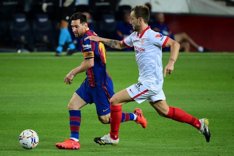 Lionel Messi (Barcelona) dan Ivan Rakitic (Sevilla) berebut bola di pertandingan Barcelona vs Sevilla pada lanjutan pekan kelima Liga Spanyol di Camp Nou, Senin (5/10/2020) dini hari WIB.