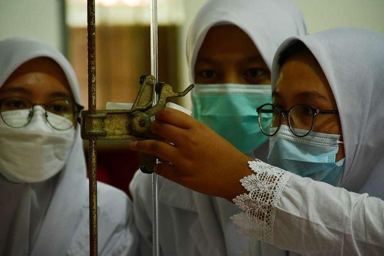 Siswa melakukan praktik analisis kimia di Sekolah Menengah Kejuruan (SMK) Negeri 13, Kota Bandung, Jawa Barat, Rabu (8/9/2021). Sebanyak 1.471 sekolah menengah atas (SMA) dan SMK di Jawa Barat mulai melaksanakan pembelajaran tatap muka (PTM) terbatas.