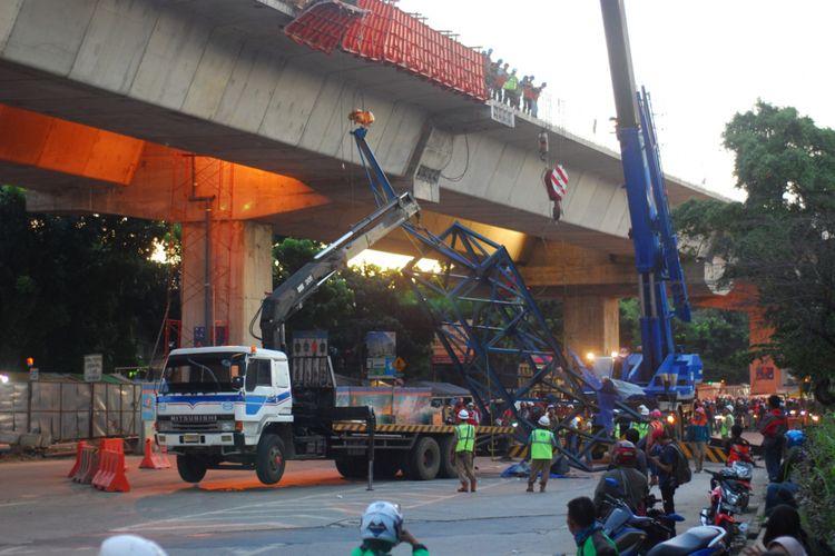 Sejumlah pekerja proyek Tol Bogor Outer Ring Road (BORR) dari PT Wijaya Karya sedang mengevakusi tower crane portable yang terjatuh saat pemasangan barrier pembatas jembatan, Kamis (26/10/2017).