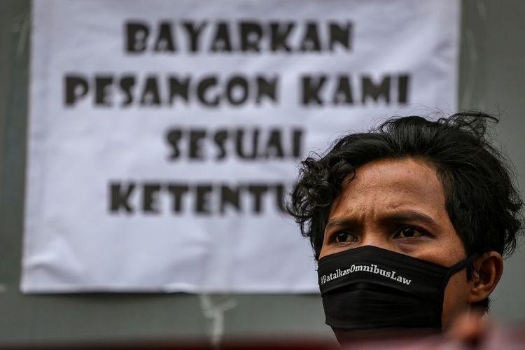 Seorang buruh menggelar aksi unjuk rasa di depan pabriknya di Benda, Kota Tangerang, Banten, Jumat (1/5/2020). Dalam aksi untuk memperingati Hari Buruh Internasional itu, massa menolak RUU Omnibus Law serta meminta pemerintah dan pengusaha untuk menjamin kelangsungan hidup buruh. ANTARA FOTO/Fauzan/pras.