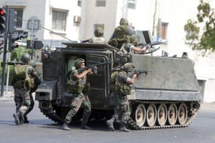 Pasukan Lebanon berlindung di balik kendaraan lapis baja meladeni tembakan dari kelompok bersenjata yang loyal kepada ulama kontroversial Sheik Ahmad al-Assir, dalam pertempuran di desa Abra, Sidon, Lebanon.