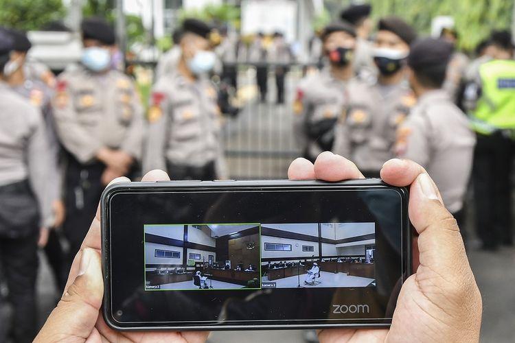 Layar telepon pintar menampilkan suasana sidang kasus pelanggaran protokol kesehatan dengan terdakwa Rizieq Shihab yang digelar secara virtual di Pengadilan Negeri (PN) Jakarta Timur, Jakarta, Selasa (30/3/2021). Sidang tersebut beragendakan mendengarkan pendapat Jaksa Penuntut Umum atas eksepsi terdakwa. ANTARA FOTO/ Fakhri Hermansyah/wsj.