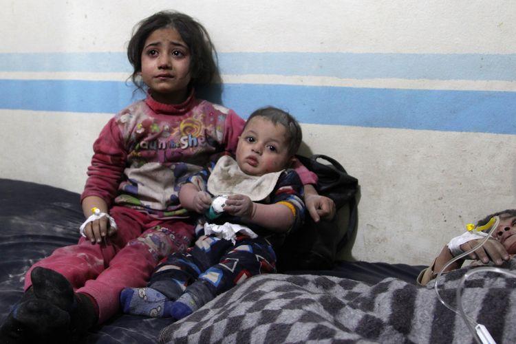 Seorang anak perempuan tengah menggendong bayi dengan di sebelah mereka, terbaring bocah laki-laki yang terluka setelah serangan udara di Idlib, Suriah, pada 11 Februari 2020.