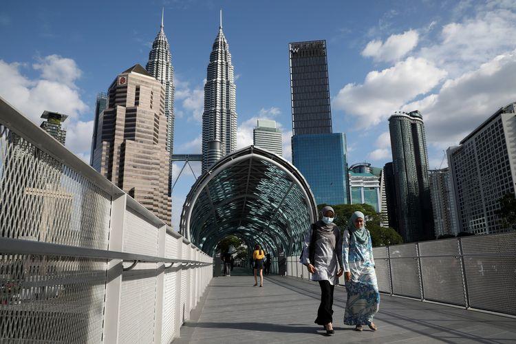 Seorang perempuan memakai masker melintas di sebuah jembatan di Kuala Lumpur, mengingat virus corona mulai merebak di Malaysia (19/2/2020).