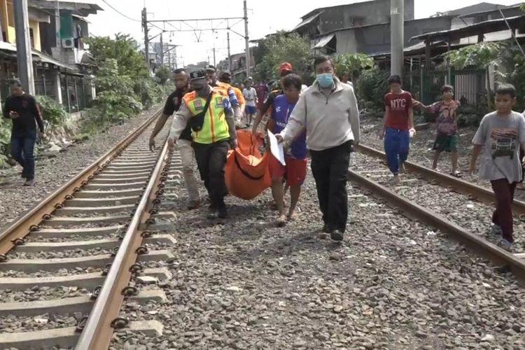 Jenazah seorang pria yang bunuh diri di perlintasan kereta api di dekat Stasiun Pesing, Grogol Petamburan, Jakarta Barat dievakuasi pada Senin (31/5/2021).