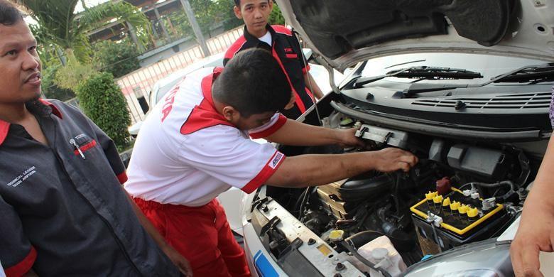 Mekanik Auto2000 sedang memeriksia kondisi mobil.
