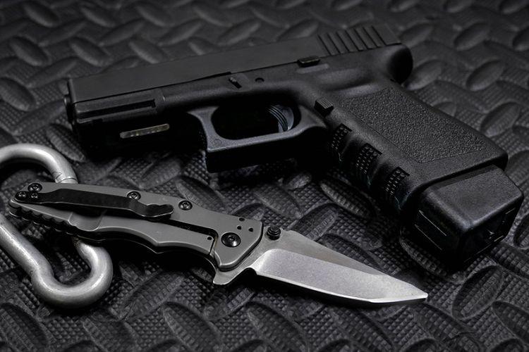 Ilustrasi pistol semi-otomatis Glock 9 milimeter dan pisau.