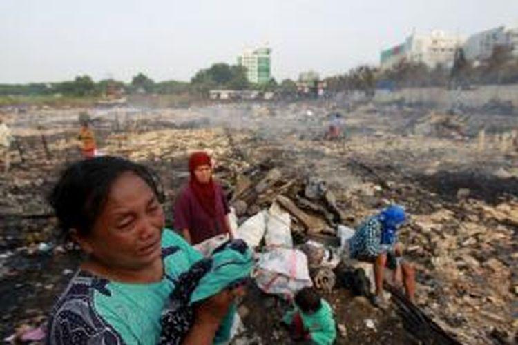 Warga menangis melihat puing bangunan rumahnya yang terbakar di Kampung Pulo Kandang, Jalan Inspeksi Kali Sunter, Kelurahan Kelapa Gading Barat, Kecamatan Kelapa Gading, Jakarta Utara, Selasa (1/10/2013). Kebakaran yang terjadi sekitar pukul 02.30 dini hari tersebut mengakibatkan sedikitnya 700 rumah terbakar.