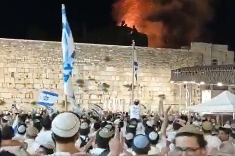 Orang-orang Yahudi Israel yang bernyanyi bersorak-sorai dan menari di depan Tembok Barat yang menunjukkan kobaran api di kompleks Masjid Al-Aqsa. [SS/Twitter/@AyOdeh]