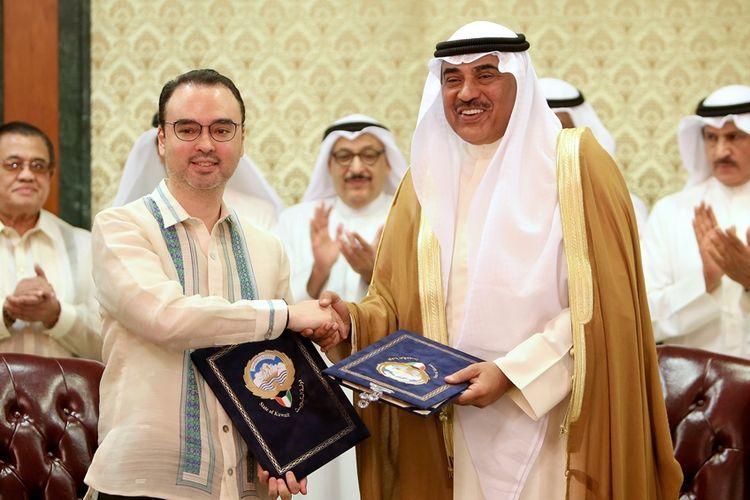 Menteri Luar Negeri Kuwait Sheikh Sabah al-Khaled (kanan) berjabat tangan dengan Menlu Filipina Alan Peter Cayetano usai penandatanganan kesepakatan pekerja rumah tangga di Kuwait City, Jumat (11/5/2018).