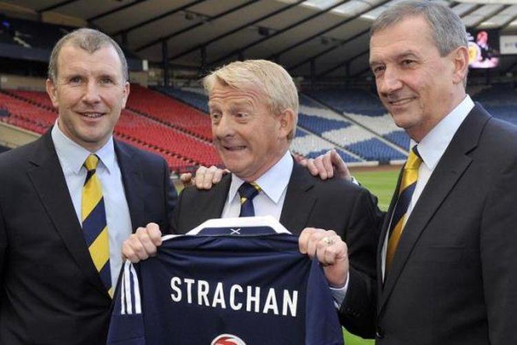 Pelatih timnas Skotlandia yang baru terpilih, Gordon Strachan (tengah), berpose dengan kostum timnas yang bertuliskan namanya, di samping Stewart Regan (kiri), Chief Executive Asosiasi Sepak Bola Skotlandia (SFA), dan Campbell Ogilvie, Presiden SFA, setelah konferensi pers di Glasgow, Selasa (15/1/2013).