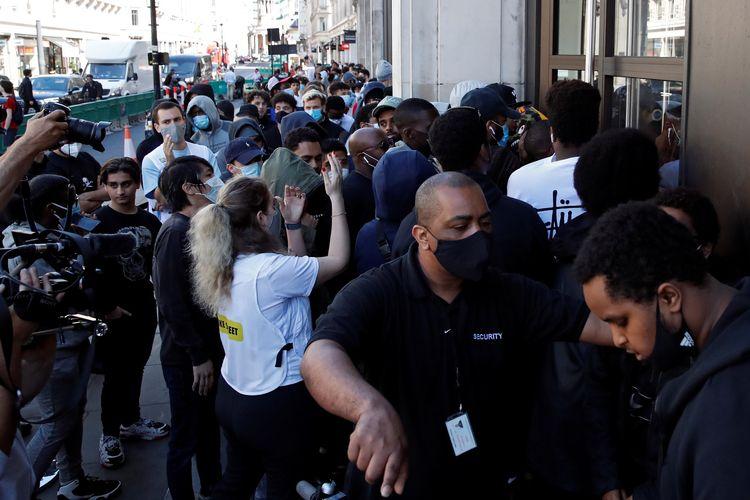 Para pengunjung berjubel dan saling dorong untuk masuk Nike Town yang dibuka lagi di Oxford Street, London, Inggris, pada 15 Juni 2020.