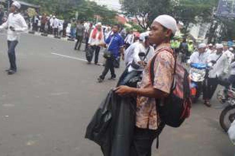 Beberapa orang dari massa yang mengikuyi demonstrasi nampak membawa kantung plastik besar berwarna hitam. Mereka menampung sampah-sampah dari pendemo untuk menjaga Jakarta tetap bersih dari sampah selama berlangsungnya demo, Jumat (4/11/2016).