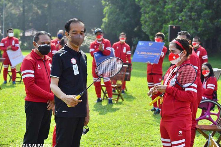 Presiden Joko Widodo menerima kenang-kenangan raket yang dipakai atlet bulu tangkis Leani Ratri Oktila saat berjuang meraih medali emas ajang Paralimpiade Tokyo 2020, di halaman belakang Istana Kepresidenan Bogor, Jawa Barat, Jumat (17/9/2021). Presiden Joko Widodo menerima kontingan Paralimpiade Tokyo 2020 di Istana Kepresidenan Bogor sekaligus menyampaikan apresiasi dan memberikan bonus kepada atlet dan pelatih yang berlaga di ajang olahraga tersebut.