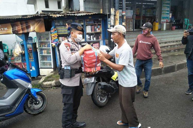 Brigade Mobil (Brimob) Polda Jawa Barat membagikan nasi bungkus kepada masyarakat yang terimbas pandemi covid-19. Nasi bungkus yang dibagikan  sebelumnya dipesan di warung nasi milik warga.