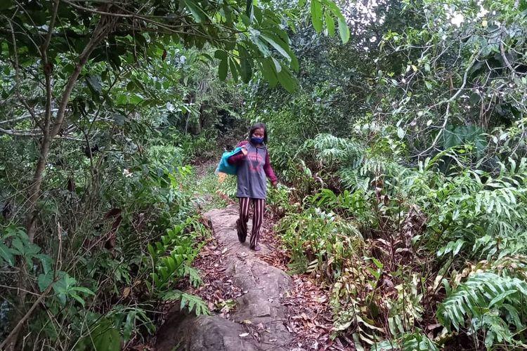 Berta Bua'dera saat berjalan kaki menyusuri jalan setapak yang ia lintasi selama 11 tahun sejak 2009 di Kampung Berambai Kecamatan Samarinda Utara, Kota Samarinda, Kaltim, Rabu (28/10/2020).