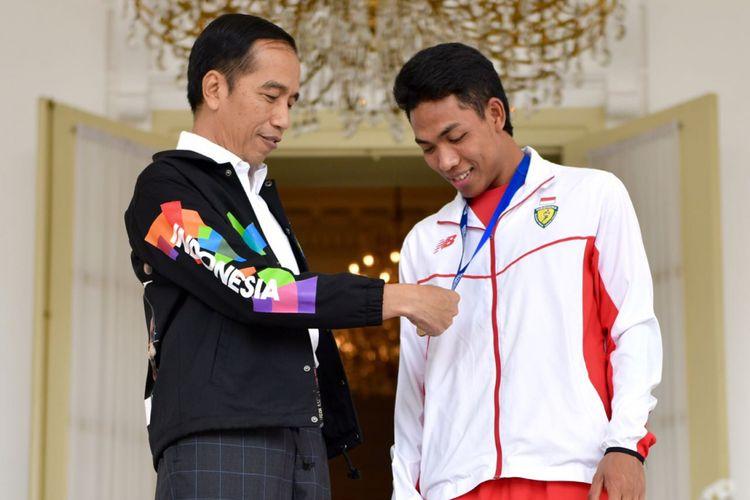 Presiden Joko Widodo dan juara dunia lari 100 meter under 20 Lalu Muhammad Zohri saat jalan-jalan di Istana Presiden Bogor, Jawa Barat, Rabu (18/7/2018).