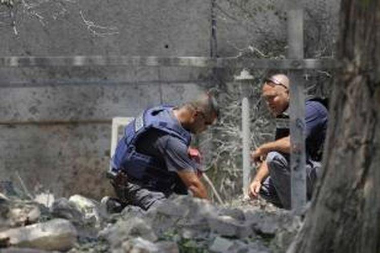 Penjinak bom Israel memeriksa kerusakan setelah sebuah roket ditembakkan oleh militan Palestina dari Jalur Gaza menghantam halaman di luar rumah di kota pelabuhan Asdod, 15 Juli 2014. Brigade Ezzedine al-Qassam, mengklaim telah menembakkan delapan roket ke Asdod.