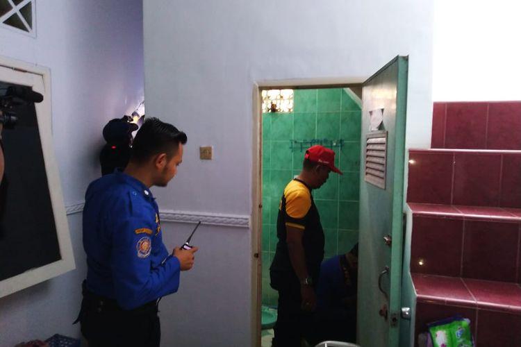 Petugas Damkar saat melihat kamar mandi rumah kos mahasiswa yang terdapat kulit ular
