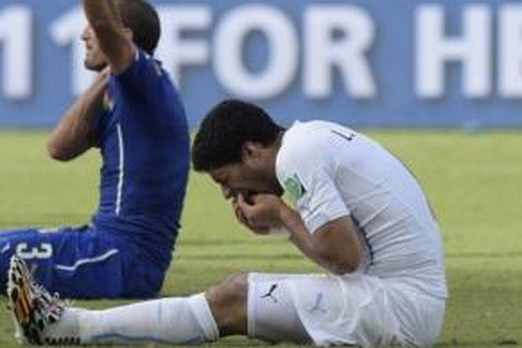 Striker Uruguay, Luis Suarez (kanan), memegang giginya usai sebuah insiden dengan bek Italia, Giorgio Chiellini (kiri), pada laga Grup D Piala Dunia 2014 di Arena das Dunas, Natal, Selasa (24/6/2014).
