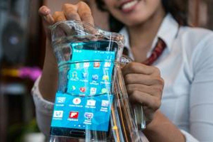 Galaxy S5 direndam di dalam wadah berisi air dalam acara Media Pre-Briefing di Jakarta, Rabu (19/3/2014). Perangkat tersebut masih bisa berfungsi dengan normal setelahnya.