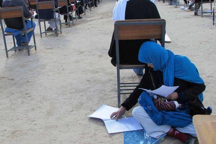 Jahan Taab (25) duduk di lantai ruang kelas Institut Pendidinkan Tinggi Nasirkhosraw, kota Nilli, Daykundi, Afghanistan, untuk mengikuti ujian masuk kuliah sambil menyusui bayinya. (Yahya Erfan via CNN)