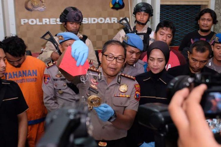 Petugas menunjukkan barang bukti pelaku pembunuhan di Ganting Sidoarjo.