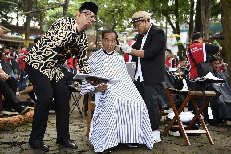 Presiden Joko Widodo (tengah) didampingi Gubernur Jawa Barat Ridwan Kamil (kiri) mengikuti potong rambut massal di area wisata Situ Bagendit, Garut, Jawa Barat, Sabtu (19/1/2019). ANTARA FOTO/Puspa Perwitasari/foc.
