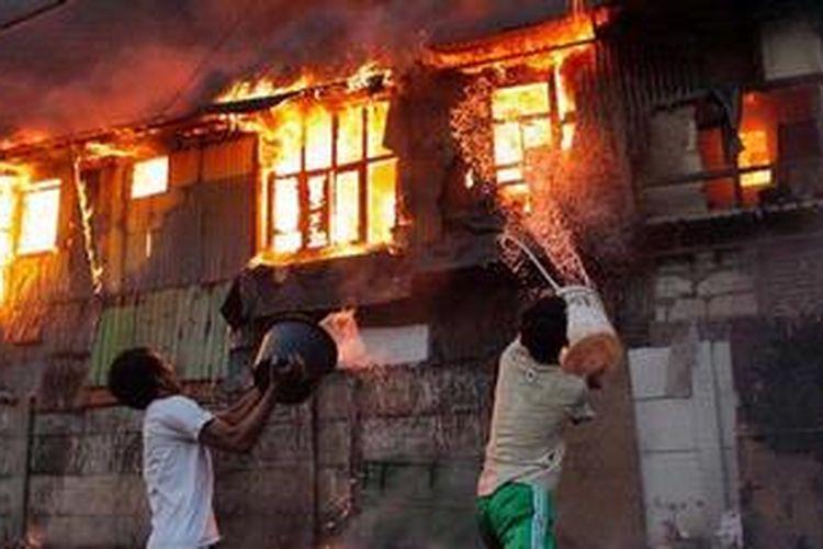 Warga berusaha memadamkan api dengan alat seadanya pada kebakaran yang melalap pemukiman di Kampung Duri Selatan, Tambora, Jakarta Barat, Kamis (7/2/2013). Akibat besarnya api puluhan rumah yang berada di tepi rel kereta itu habis terbakar.