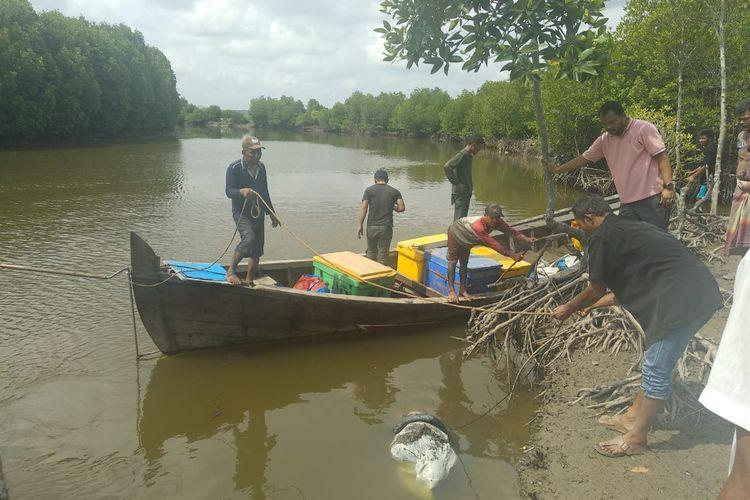 Warga mengevakuasi mayat dalam karung di Desa Geulumpang Payung, Kecamatan Sungai Raya, Kabupaten Aceh Timur, Selasa (1/10/2019)