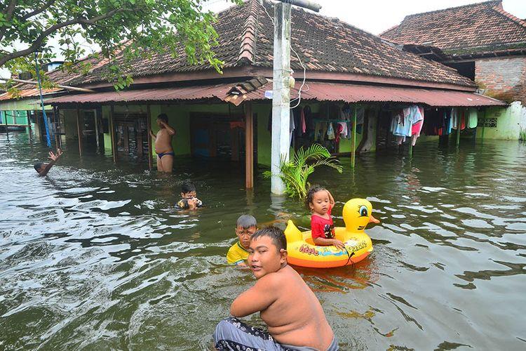 Sejumlah anak bermain di genangan banjir, di Dukuh Tanggulangin, Desa Jati Wetan, Jati, Kudus, Jawa Tengah, Senin (8/2/2021). Menurut data dari Badan Penanggulangan Bencana Daerah (BPBD) setempat, banjir dengan ketinggian hingga 170 centimeter yang merendam 13 desa di kecamatan Mejobo, Jati dan Undaan lebih dari sepekan akibat curah hujan tinggi serta meluapnya sungai Lusi dan Wulan itu menyebabkan sebanyak 17.614 jiwa terdampak dan 4.420 rumah terendam serta 576 warga mengungsi.
