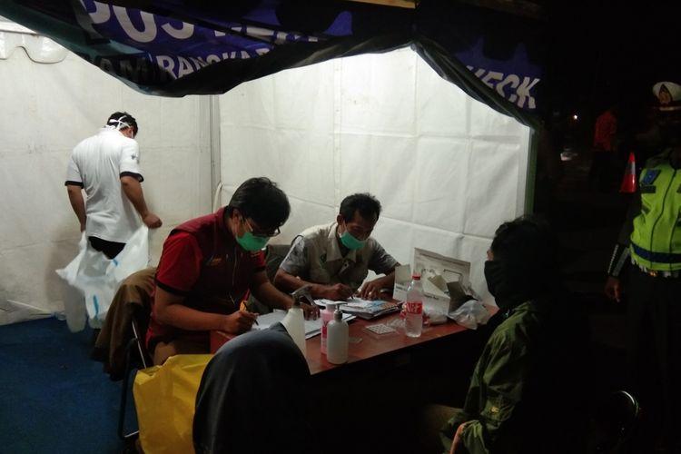 Petugas kesehatan tengah melakukan tes swab antigen kepada pemudik.dengan tujuan Pemalang di Pos Penyekatan Tanjungpura, Karawang, Selasa (11/5/2021).