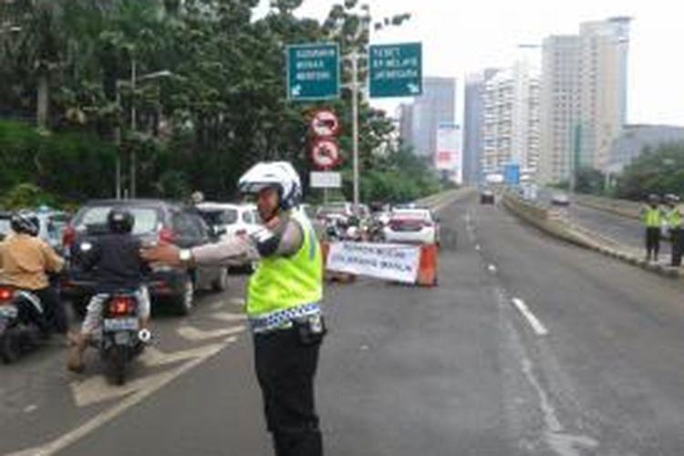 Suasana di jalur masuk Jalan Layang Non Tol (JLNT) Casablanca, Jakarta, Senin (3/2/2014). Pasca kecelakaan maut yang terjadi di lokasi tersebut, saat ini, JLNT Casabalnca dipasangi spanduk himbauan dan dijaga oleh polisi lalu lintas.