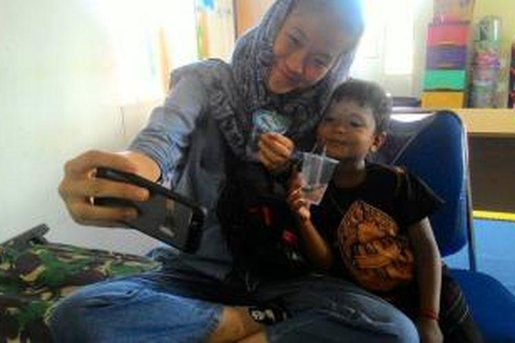 mahasiswi, jurusan Komunikasi, Nanyang Technological University (NTU) Singapura berfoto bersama anak Rohingnya di lokasi penampungan Blang Adoe, Aceh Utara, Aceh, Jumat (11/12/2015). Mereka membuat film dokumenter tentang masyarakat Aceh yang membantu warga Rohingnya. Film dengan judul Peumulia Jamee (memuliakan tamu) itu kini sedang diproduksi.