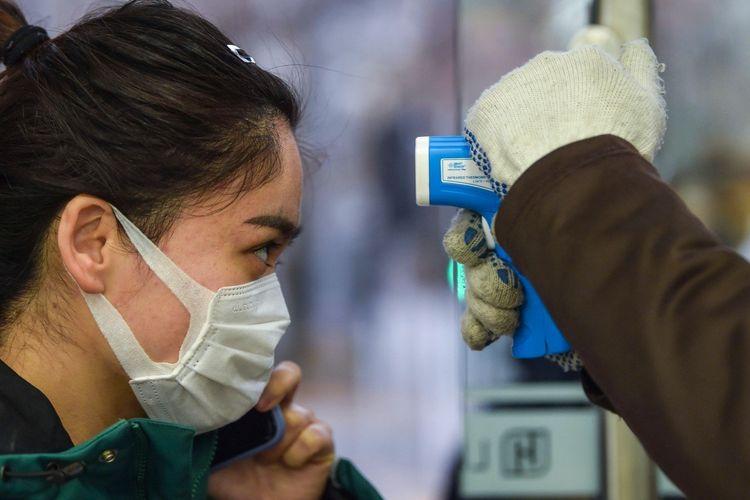 Seorang warga sedang dicek suhu tubuh menggunakan senjata termometer saat memasuki supermarket di Shanghai, China.