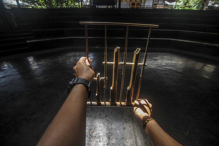Seorang instruktur memegang angklung di aula pementasan yang kosong di Saung Angklung Udjo, Bandung, Jawa Barat, Minggu (24/1/2021). Pandemi membuat aktivitas bisnis pariwisata di Saung Angklung Udjo cukup terpuruk dengan hanya dikunjungi tak lebih dari 20 orang dalam sepekan, padahal saat kondisi normal mampu menarik hingga dua ribu orang per hari.