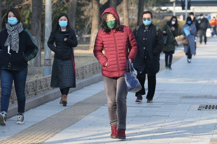 Orang-orang tetap melanjutkan aktivitas di Beijing, China, pada Kamis (5/3/2020), di tengah wabah virus corona yang melanda negara tersebut.