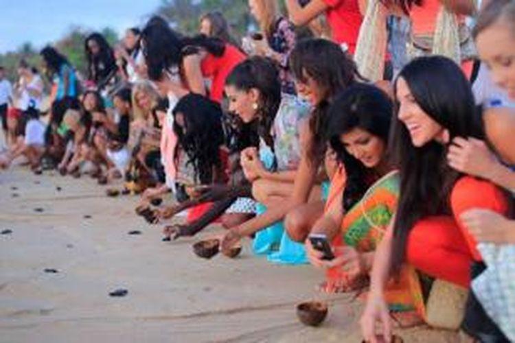 Kontestan Miss World 2013 melepas tukik atau anak penyu ke laut dalam acara konservasi kelautan di Bali, 9 September 2013.