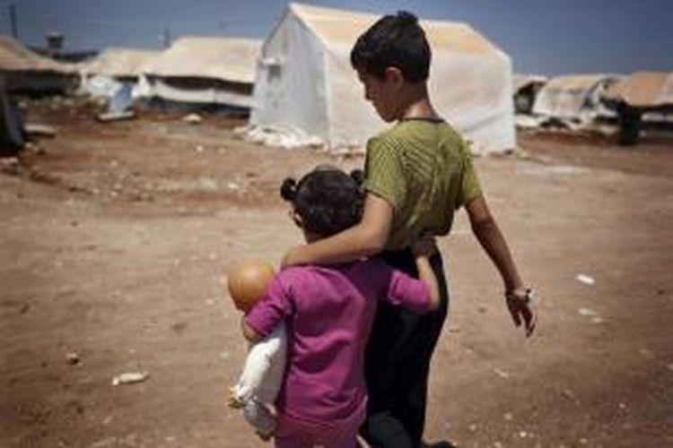Anak-anak pengungsi Suriah berjalan di kamp pengungsi al-Salam Bab di Azas, sebuah kota di utara Suriah, 15 Juli 2013. Sebanyak 5.000 orang dalam sebulan telah mati dalam perang Suriah yang menjadi krisis pengungsi terburuk sejak Genosida Rwanda 1994.