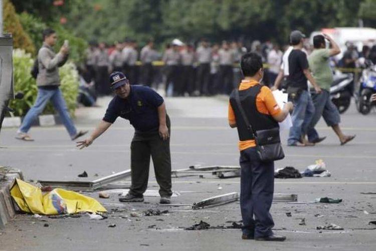 Polisi memeriksa puing-puing di lokasi setelah ledakan menghantam kawasan Jalan MH Thamrin, Jakarta Pusat, 14 Januari 2016. Serangkaian ledakan menewaskan sejumlah orang, terjadi baku tembak antara polisi dan beberapa orang yang diduga pelaku.