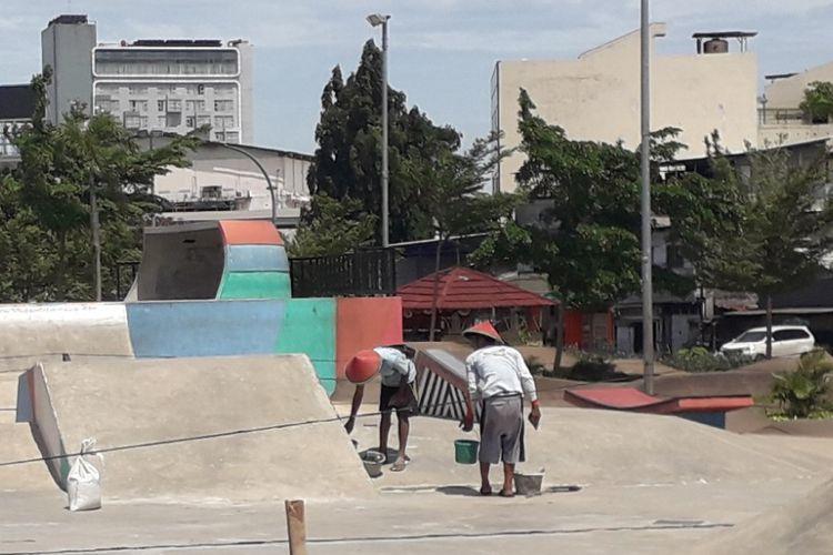 Dua orang pekerja tengah memperbaiki arena skateboard di Ruang Terbuka Hijau Kalijodo, Kamis (15/11/2018).