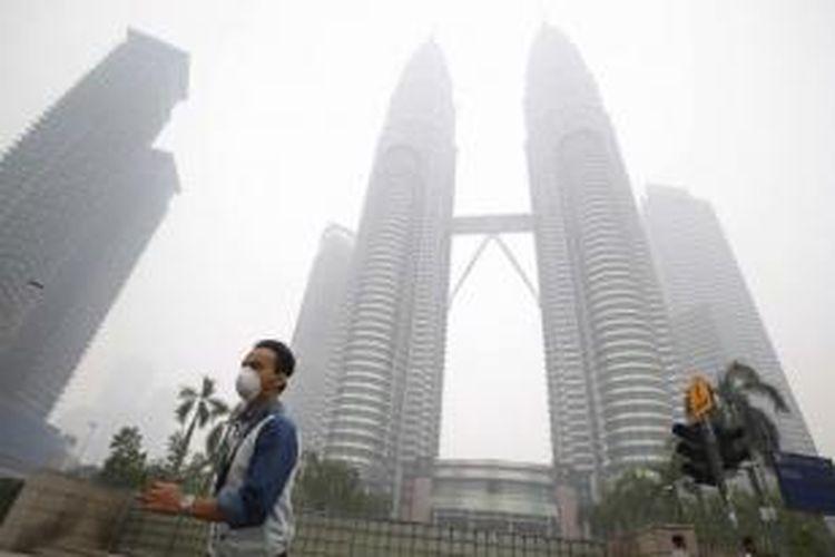 Seorang pria mengenakan masker ketika melintas di dekat Petronas Twin Towers yang tengah disellimuti kabut asap di Kuala Lumpur, Malaysia, 14 September 2015. Kabut asap berasal dari kebakaran hutan dan lahan di Sumatera, Indonesia.