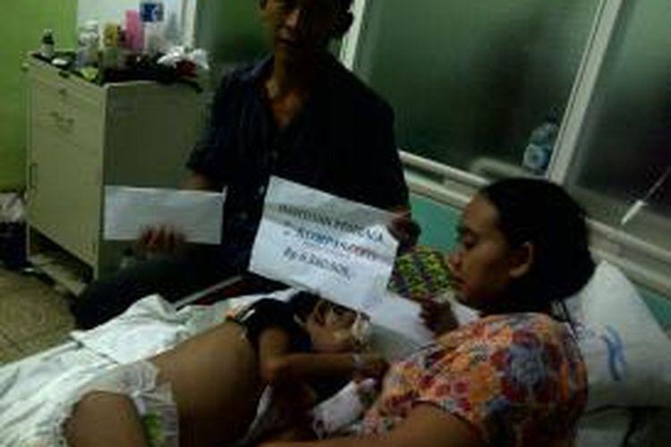 Nano (43) ayah Sandi Septiono (7) penderita tumor mata saat menerima bantuan dari pembaca Kompas.com di ruang perawatan anak lantai 2 RSUP Dr Kariadi Semarang, Jumat (18/10/2013) petang