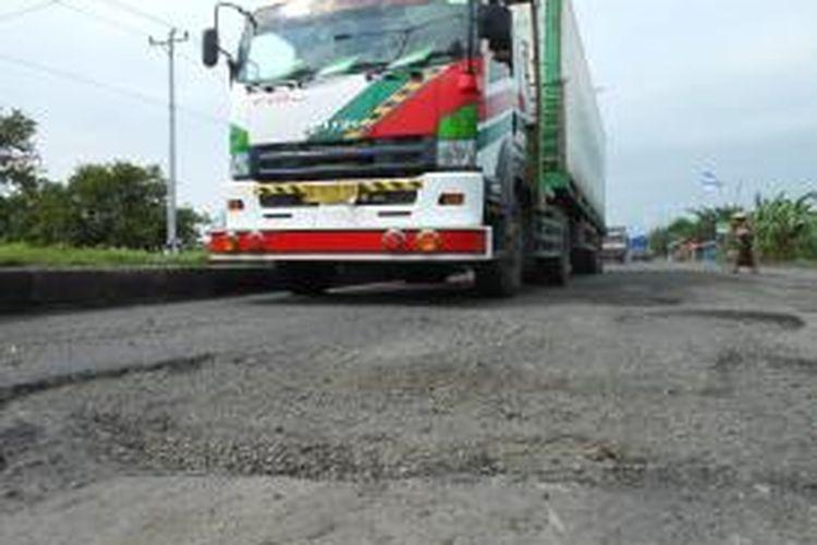 Truk dari arah Kudus saat melintas di jalan lingkar Demak yang berlubang, Sabtu (1/2/2014)