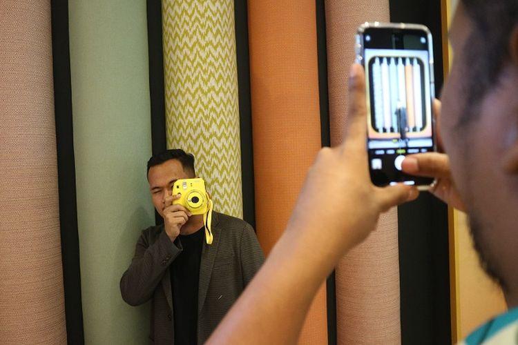 Salah satu pengunjung di Ibis Styles Jakarta Tanah Abang sedang berfoto dengan latar belakang kain gulung.
