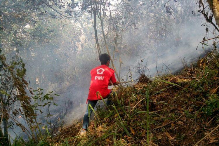 Relawan PMI mencoba memadamkan api yang membakar lahan hutan lereng utara Gunung Merbabu di Kecamatan Ampel, Kabupaten Boyolali, Jawa Tengah, Jumat (12/10/2018).