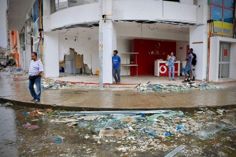 Penduduk dan penjaga toko terlihat berada di sebuah kawasan pertokoan setelah topan Idai melanda Beira, Mozambik, pada Minggu (17/3/2019). (AFP/ADRIEN BARBIER)