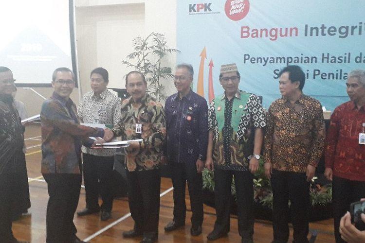 Wakil Ketua KPK Alexander Marwata menyerahkan hasil Survei Penilaian Integritas kepada para peserta survei di Kantor KPK, Selasa (30/9/2019).