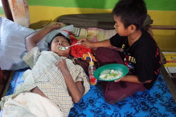 Muhammad Gunadiono (11), seorang murid kelas 5 SDN Gedongombo 2, Kecamatan Ploso, Kabupaten Jombang, Jawa Timur, saat menyuapi ibunya yang hanya bisa terbaring diatas ranjang akibat stroke.