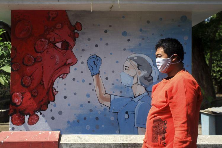 Warga melintas di dekat mural bergambar tenaga medis dan Virus Corona di kawasan Bantul, Yogyakarta, Selasa (23/6/2020). Mural yang dibuat oleh warga itu mengingatkan warga agar waspada terhadap Covid-19 sekaligus mendukung perjuangan tenaga medis yang menjadi garis terdepan dalam penanganan COVID-19.